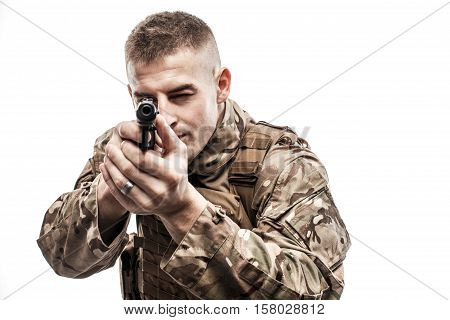 Young man wearing military uniform and aiming with handgun on white background.