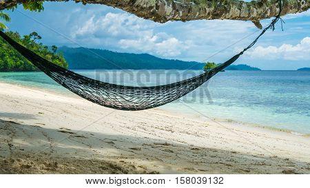 Hammock on the Beach, Batu Lima, Coral Reef of an Homestay Gam Island, West Papuan, Raja Ampat, Indonesia.