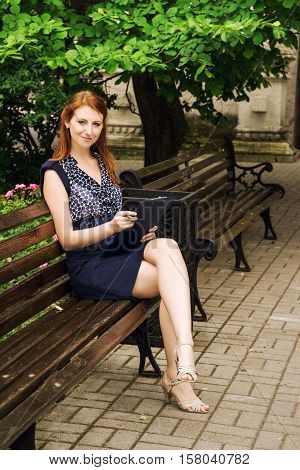 Beautiful girl writes on a clipboard at park. Female student sitting on wooden bench