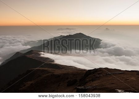 Picturesque Landscape Of Mountain Valley Filled With Curly Clouds At Sunrise. Dramatic Hill Lit Up B