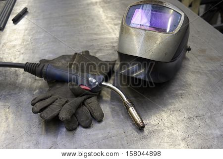 Welder Equipment, Torch, Gloves And Shield On A Metal Plate