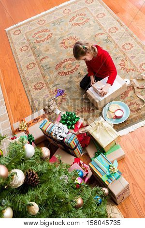 Cute Five Year Old Girl Wrapping A Christmas Gift