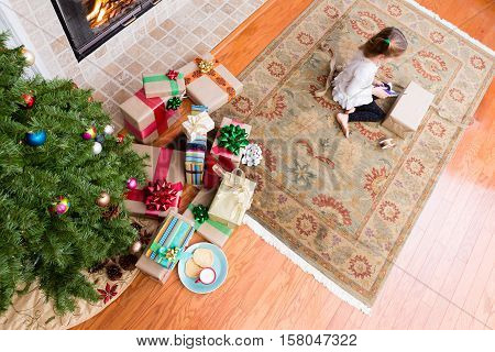 Little Girl Wrapping Xmas Gifts In Her Living Room
