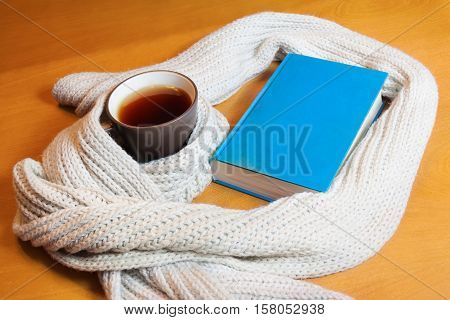 Cup of tea, woolen scarf  and book