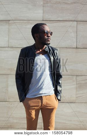 Fashion African Man Wearing A Sunglasses And Black Rock Leather Jacket Over Textured Background Even