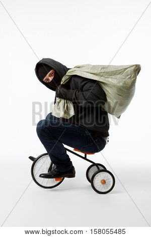 Thief in mask riding bicycle