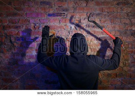 Burglar surrenders against brick wall