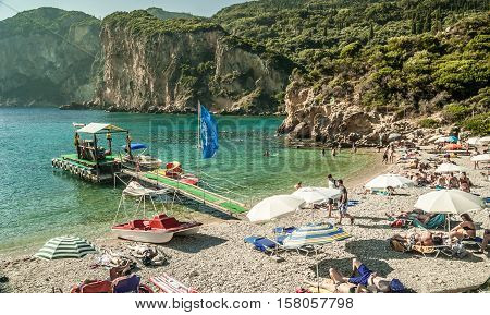 CORFU ISLAND, GREECE - August 10, 2014: Beautiful beach of Paleokastritsa. Tourists enjoying a nice summer day at the beach. Kerkyra island
