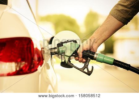 Hand refilling the car with fuel. Refuel station