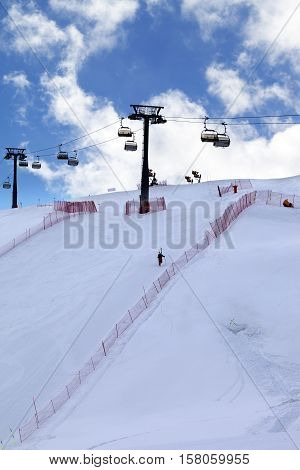 Skier Ascend On Snow Ski Slope And Ski-lift At Evening