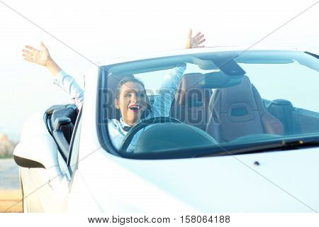Freedom - happy free woman in cabriolet cheering joyful with arms raised. Woman going on road trip travel on summer day