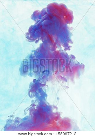 Color drop underwater creating a silk drapery. Ink swirling underwater. Cloud of colorful ink. Blue and magenta mix into violet