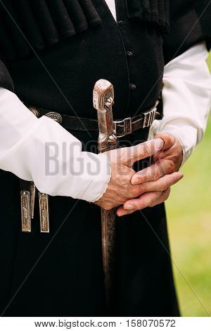 Close Up Hands Of Elder Georgian Man In National Clothes. Culture Of Georgia Country. On His Belt Dagger Hanging. Silver Belt With A Weapon, A Dagger And Patronnitsey.