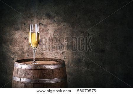 Glass of white wine on wooden barrel on dark background