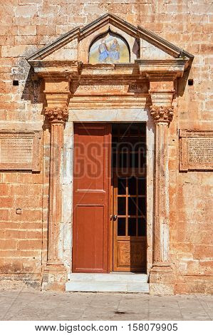 Portal and wooden door of an Orthodox monastery on the island of Crete Greece