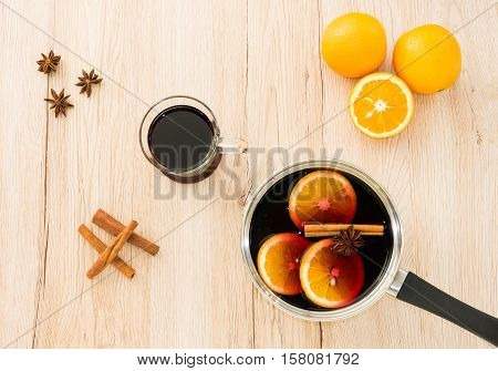 Stainless steel pot with hot freshly prepared homemade mulled wine a drinking glass filled with mulled wine cinnamon sticks star anise and oranges on light brown wooden background.