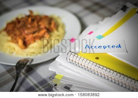 Accepted; Stack Of Documents. Working Or Studying While Eating.