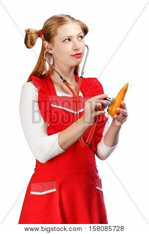 Young beautiful housewife in bright red apron with funny ponytails holds healthy natural carrot and listens it with a stethoscope isolated on white background.