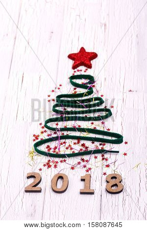 Christmas Tree Made Of Ribbons And Toys Lies On White Table Over Wooden Number 2018