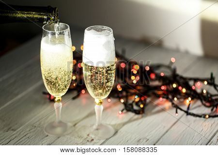 Champagne Pours From The Bottle In A Glass Standing Behind Christmas Garland