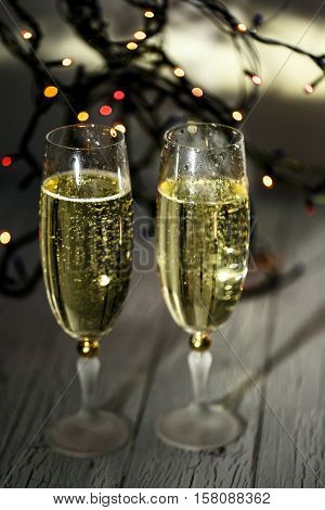 Sparkling Glasses With Champagne Stand On White Wooden Floor