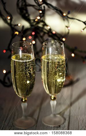 Christmas Garland Of Lights Hangs Behind Champagne Flutes