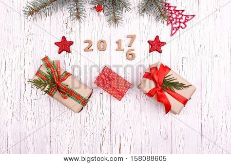 Fir Branch Lies Over Wooden Numbers 2016 And 2017 And Red Present Boxes