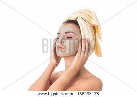 cutie girl takes care her skin with cleansing mask on face and towel on head isolated on white background. Health care concept. Body care concept. Young woman with healthy skin.