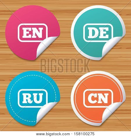 Round stickers or website banners. Language icons. EN, DE, RU and CN translation symbols. English, German, Russian and Chinese languages. Circle badges with bended corner. Vector