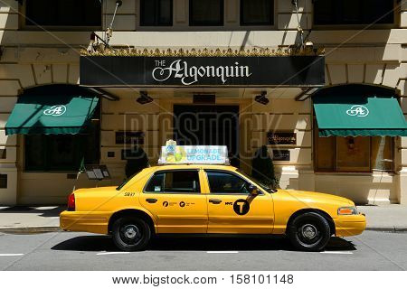 NEW YORK CITY - MAY 26, 2014: Yellow Ford Crown Victoria Taxicab in front of the Algonquin Hotel. This Hotel is a historic hotel built in 1902 on 59 W 44th Street in Manhattan, New York City, USA.