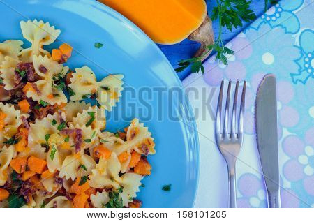 Italian Wholemeal Pasta Farfalle Butterfly Bow-tie with Butternut Squash and Prosciutto. Pasta with pumpkin sauce bacon and fresh parsley on blue wooden background. Italian cuisine concept. Top view.
