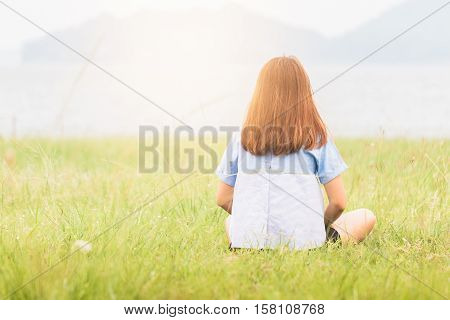 Young Woman Sitting At Relax Pose Or Freedom Pose Or Chill Pose On The Meadow During Sunrise At Morn
