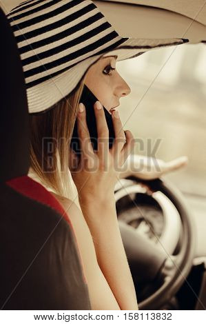 Distracted driver. Young attractive woman using mobile phone talking while driving the car.