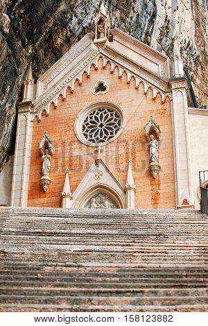 Stone steps of stairs to Ancient Madonna della Corona santuario facade under rocks in high mountains. Veneto region. Italy. Famous touristic landmark
