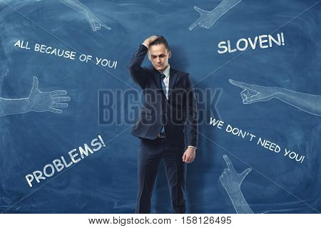An embarrassed businessman standing and running his hand through his hair near the dark blue wall with hands pointing to him and blaming words drawn on it. Face serious challenges. Business difficulties. Get into trouble.