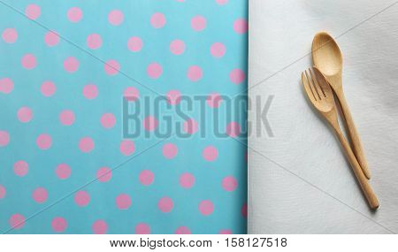Wooden spoon and fork on white paper and paper placemat pattern pink dot and cyan background. Menu set Concept