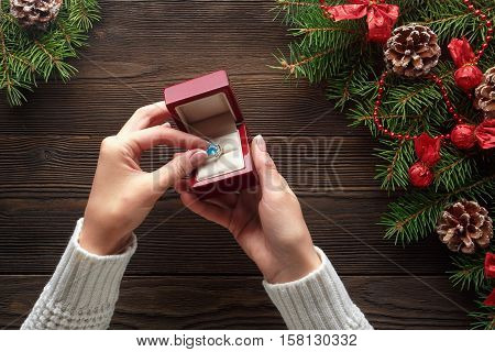 Christmas background. Engagement ring in female hands among Christmas decorations on wood background. Romance, jewelry concept - woman hands with wedding ring in gift box. Gift on Valentine's Day