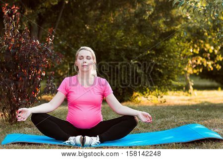 Cute pregnant woman practicing yoga outdoor. Adult expectant girl meditating at nature, sitting on karemat. Nirvana, calm, relaxation concept