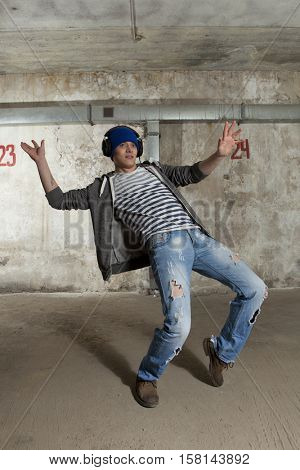 Young man break dancing on wall background