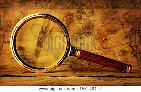 Vintage brass magnifying glass and old map. Nautical or historical concept.