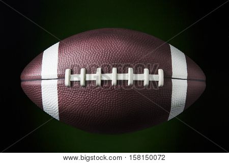 portrait of a american football ball in dark background