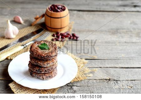 A stack of fried bean cutlets on a plate. Vegetarian cutlets cooked from red beans. Raw red beans in small barrel, garlic, fork, knife on old wooden background with copy space for text. Vintage style