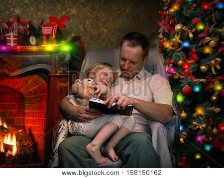 Christmas story by the fireplace. Dad reads a book a little daughter. Christmas tree festive interior of the house. Christmas Eve