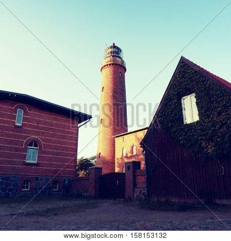 Shinning Old Lighthouse Above Houses Before Sunset. Tower Illuminated With Strong Warning Light