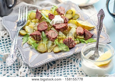 Warm salad with potatoes pickles chicken liver and mayonnaise