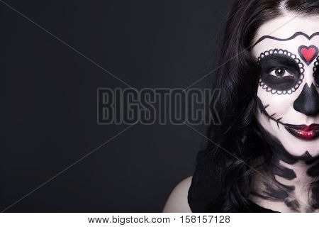 Close Up Portrait Of Smiling Woman With Halloween Skull Make Up Over Grey