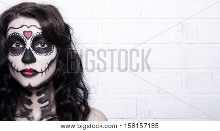 Woman With Creative Halloween Skull Make Up Over White Brick Wall