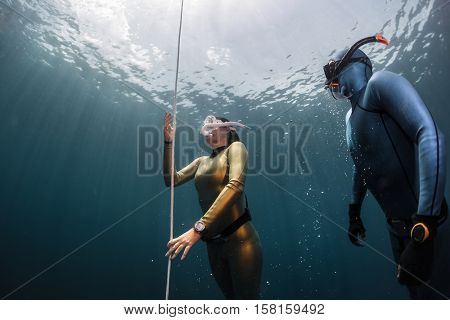Two ladies freedivers ascending along the rope from the depth. Coach watching student