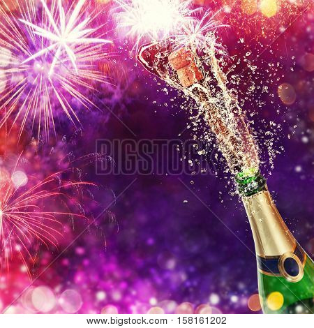 Splashing bottle of champagne with glasses over blur colored background. Celebration concept, free space for text