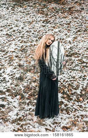 Young woman in black dress holding big oval mirror. Trees are reflected in the mirror. Outdoor shot. Winter, snowy weather. Mystic gloomy gothic style